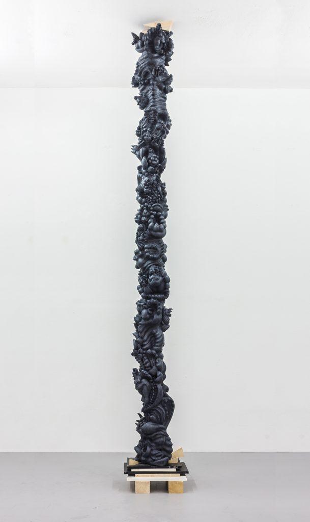 ornamentale pflanzen und frauen bilden eine gerade säule.in blaugrauer patina