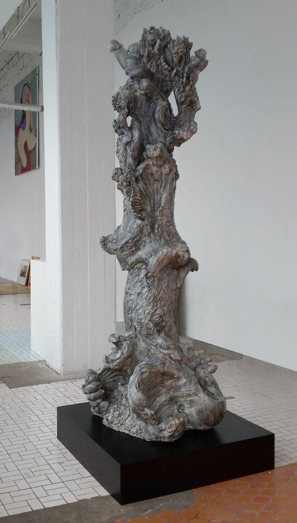 miriamlenk amorphe säule aus gipsfragmente von barocken pflanzen- und frauenfiguren neben rauhen kanten und werkspuren. blau-graue lasur