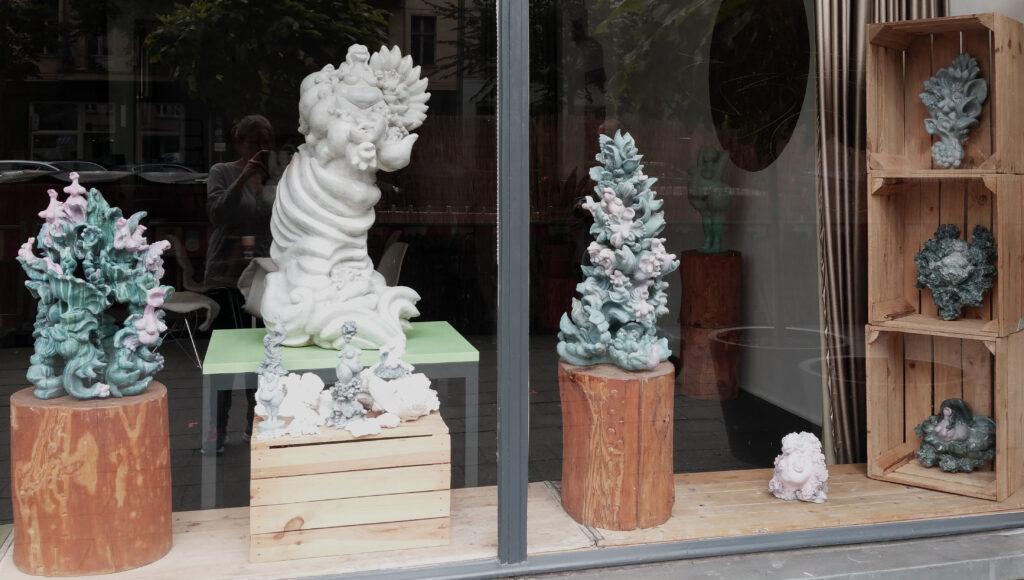 Keramiken aus wild wuchernden Pflanzen- tier-und barocken ornament-elementen in blau-grün-pinker und weisser patina.ausstellungsansicht im schaufenster