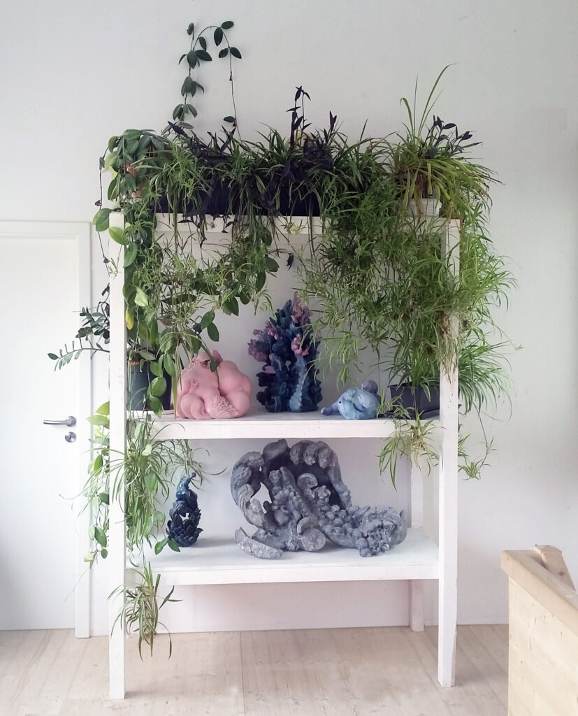 miriamlenk installation in einem holzregal mit keramiken und pflanzen.die keramiken sind mischwesen aus frau, fisch und pflanze.240x 150x 75cm 2021